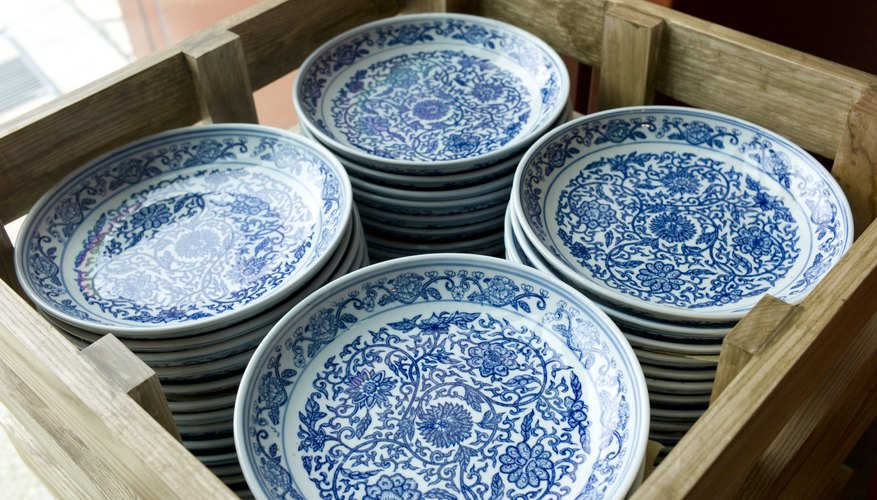 China porcelain plates packed inside of a wooden crate.