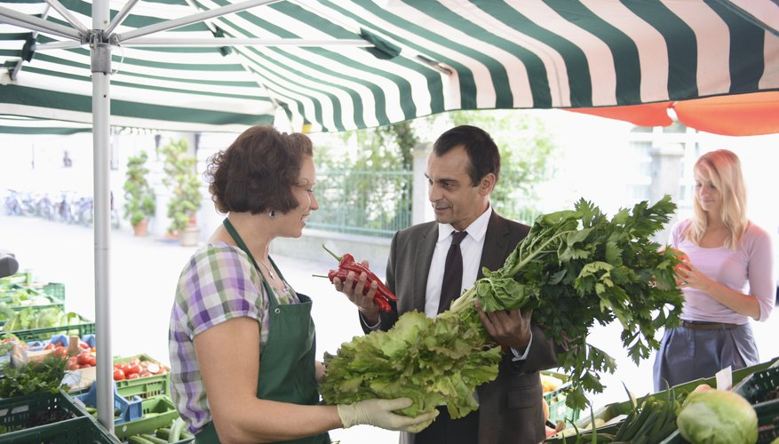 Mature man buying vegetables from market trader