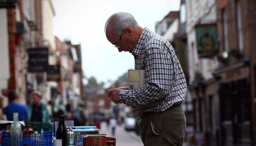 A man inspecting antiques on an outdoor table in town.