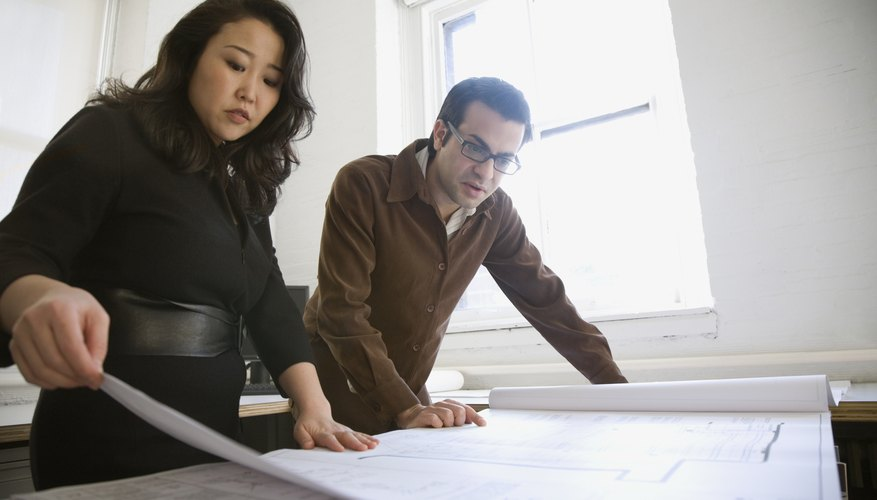 Multi-ethnic businesspeople looking at blueprints