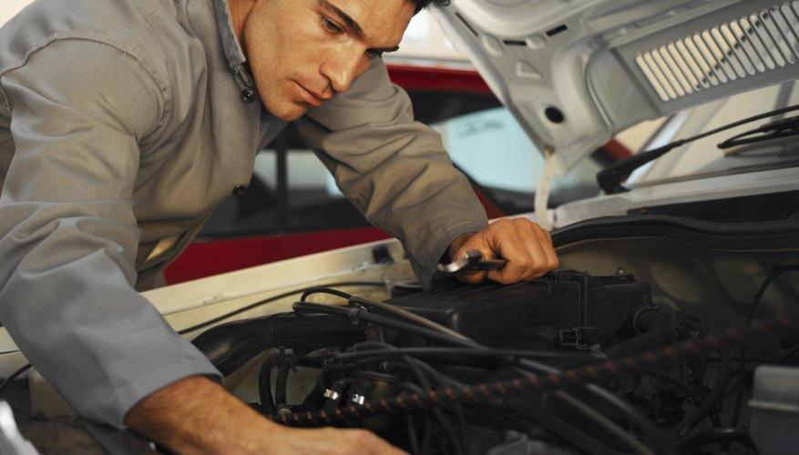 Close-up of mechanic examining bonnet of car