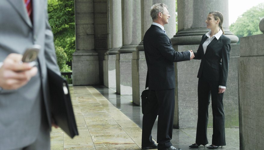 Businessman and woman shaking hands by man using mobile phone