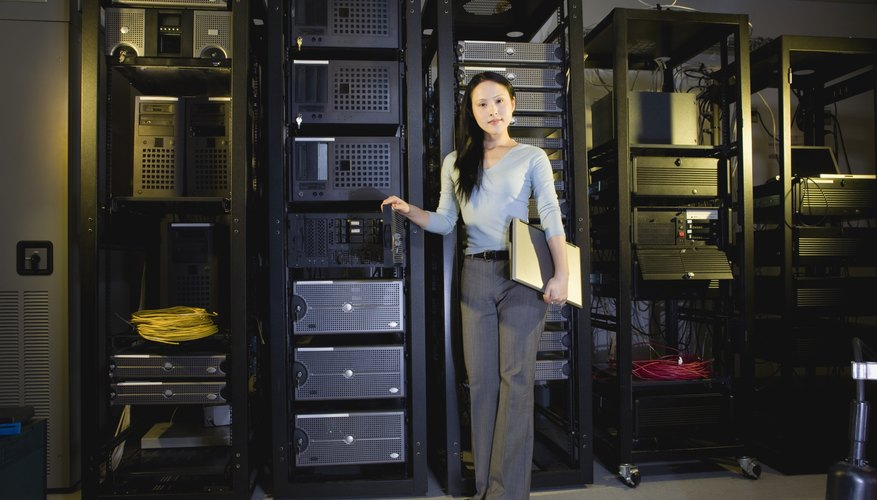 Woman holding laptop computer in server room