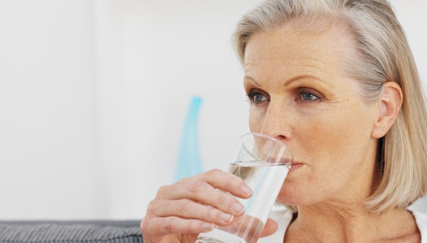Older woman drinking glass of water.