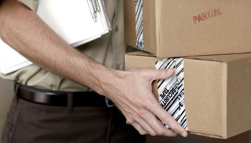 Mid section view of a man holding boxes and a clipboard