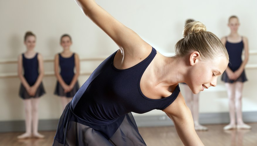 A ballerina performs a solo in front of her classmates.
