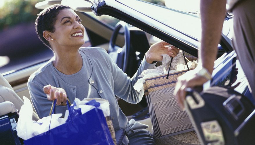 Mature woman sitting in a car carrying shopping bags