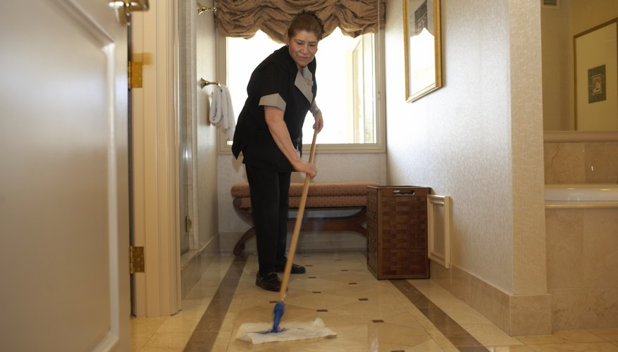Hotel maid cleaning floor in hotel room