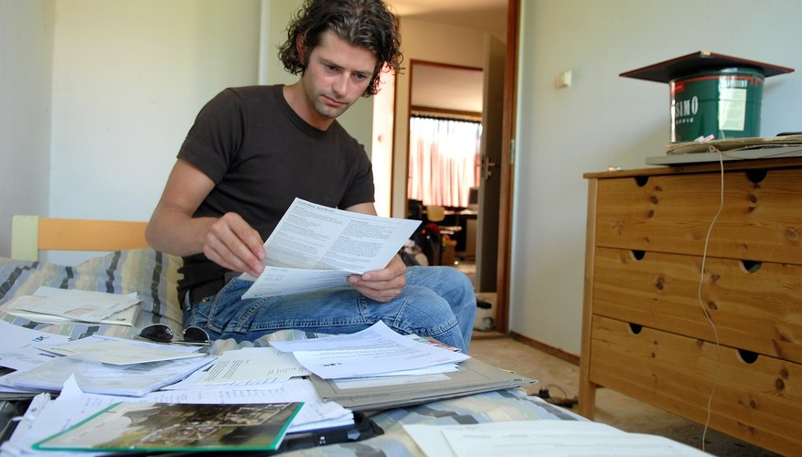 mid adult man going through paperwork on bed