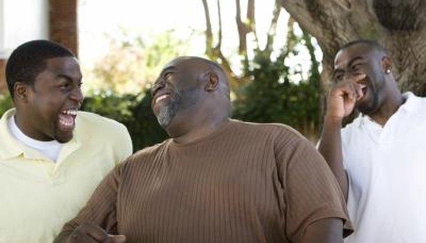 Un hombre riendo con sus dos hijos al aire libre.