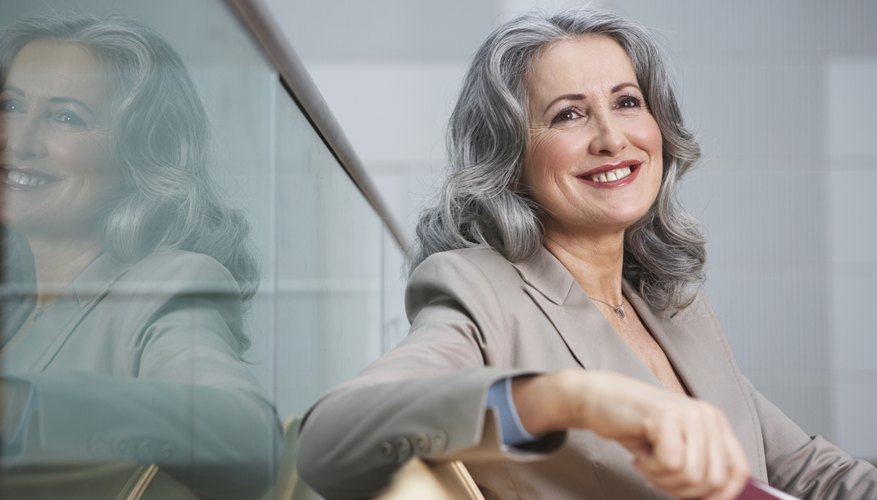 Mature businesswoman sitting in airport, smiling