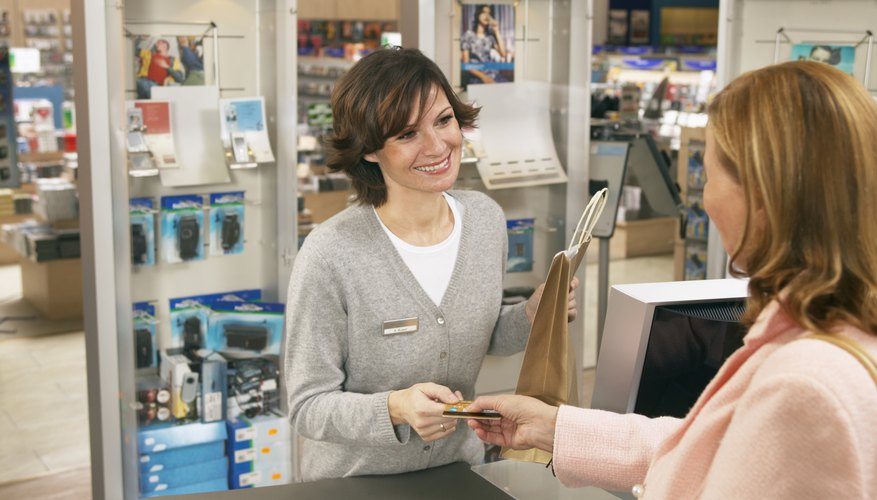 Woman passing card to shop assistant in shop