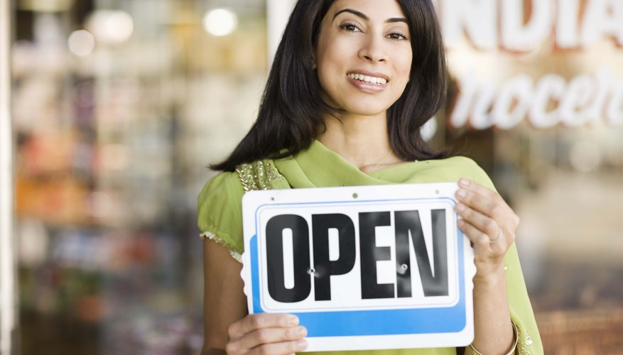 Portrait of smiling woman by storefront with open sign