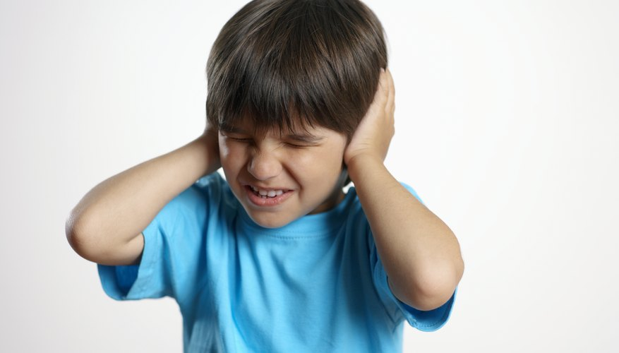 A child can react to sensory overload by covering his ears and squeezing his eyes shut.