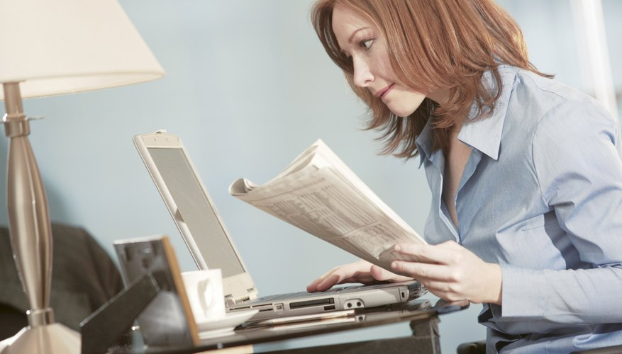 Woman with laptop holding newspaper