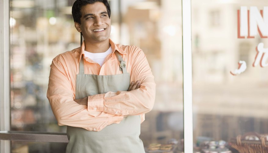 Shopkeeper smiling by storefront