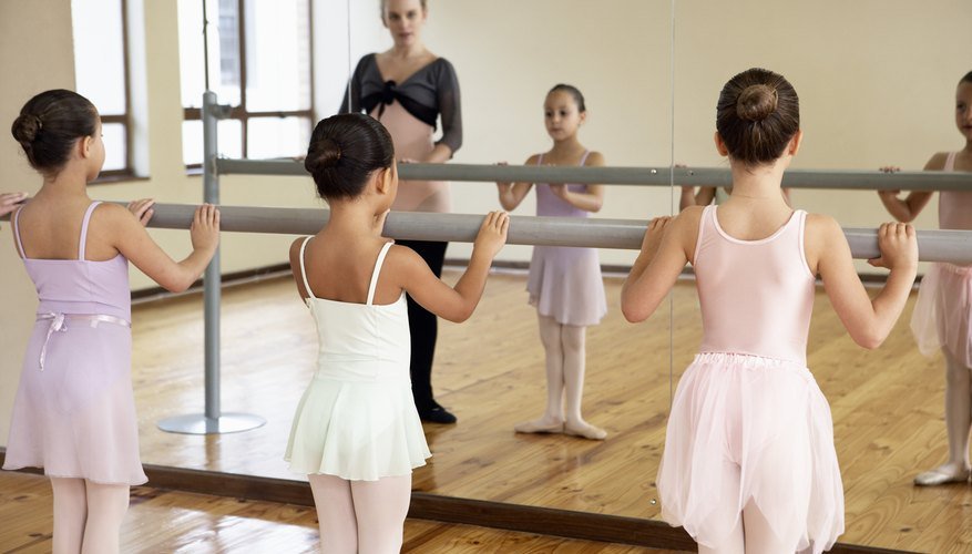 Young ballerinas holding a barre