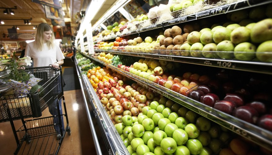 A woman is shopping in the produce section at the grocery store.