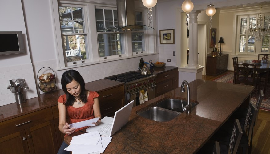 Woman working on tax paperwork in her home.