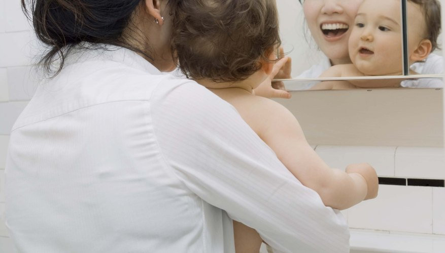 Around 12 months of age, a toddler develops self-awareness and recognizes her reflection in the mirror.