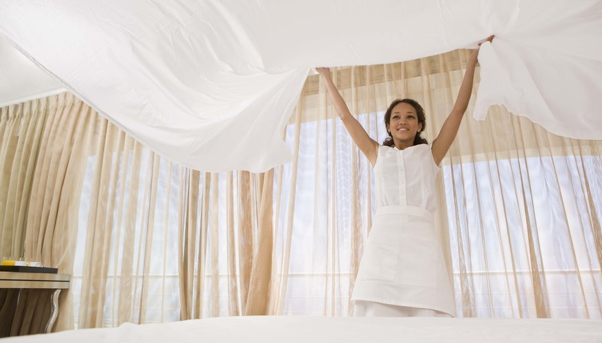Maid putting clean sheets on bed in hotel room