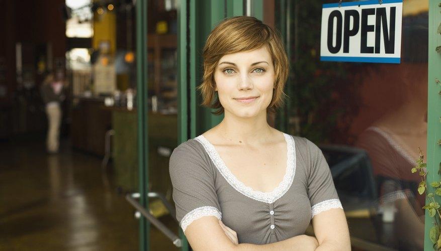 Empleada de pie frente a una tienda abierta.