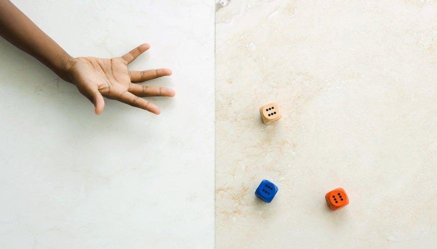 An overhead view of a child throwing three dice on a marble floor.