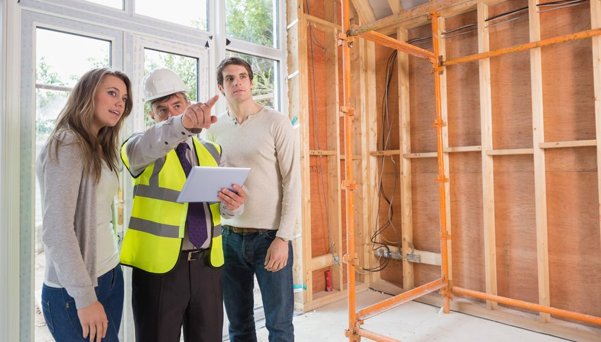 Business owners speaking with a construction worker in a building under construction
