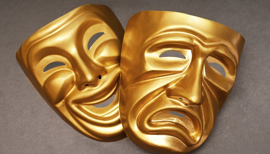 An overhead view of two dramatic gold masks representing comedy and tragedy.