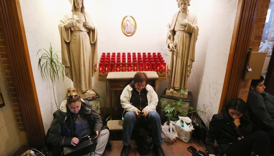 People rest and charge devices at a shelter for those affected by Superstorm Sandy at Saints Peter and Paul Church on November 1, 2012 in Hoboken, New Jersey.