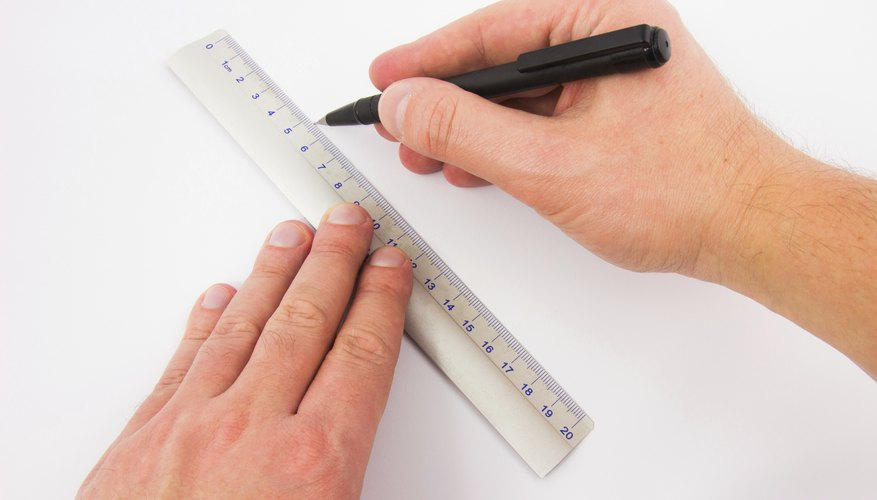 Male hands drawing line with a ruler