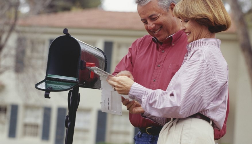 Couple checking mail in garden