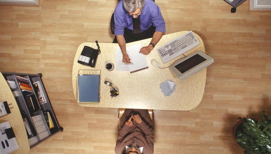 Woman and man working at desk in office, overhead view