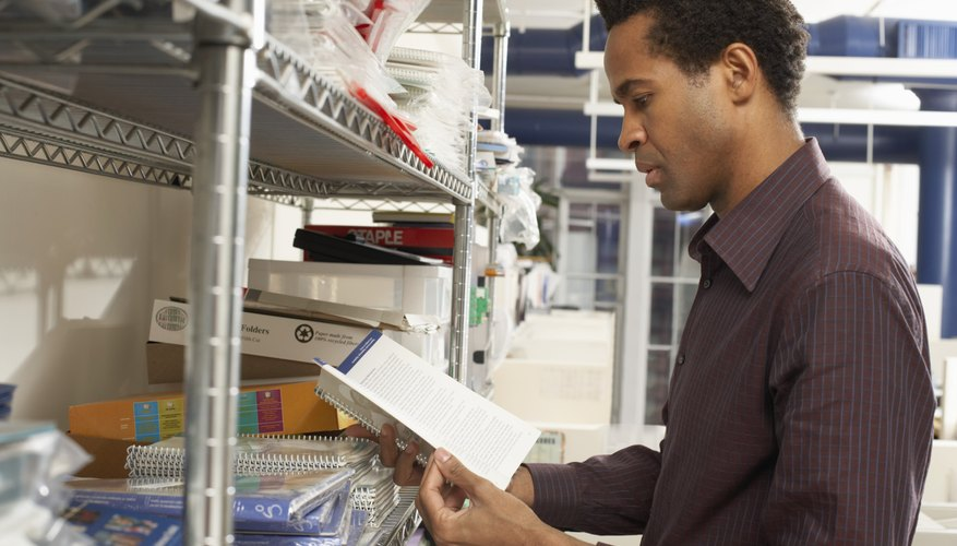 Male office worker looking at exercise book by storage shelves
