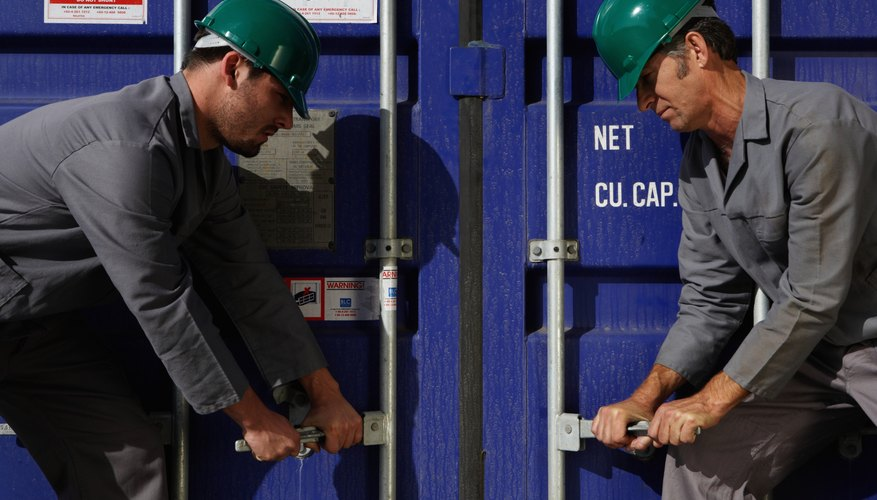 Two men opening cargo container, wearing hard hats, side view