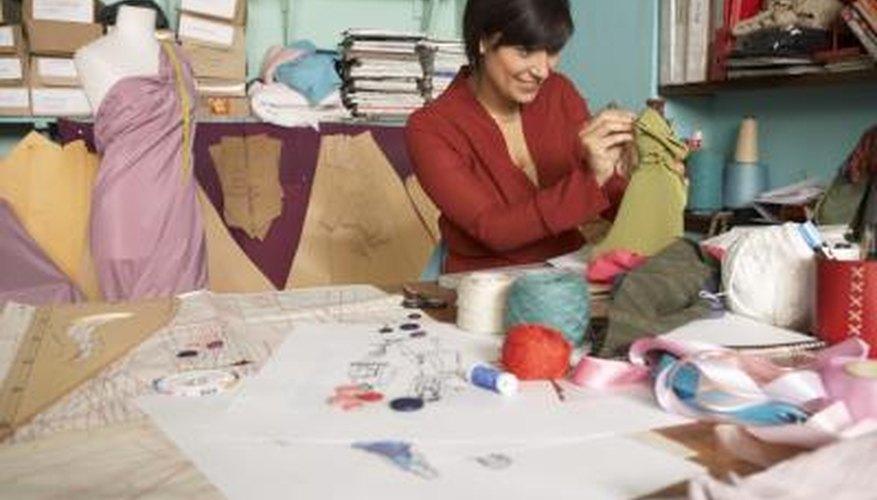 Diseñadora de moda femenina trabajando y sonriendo.