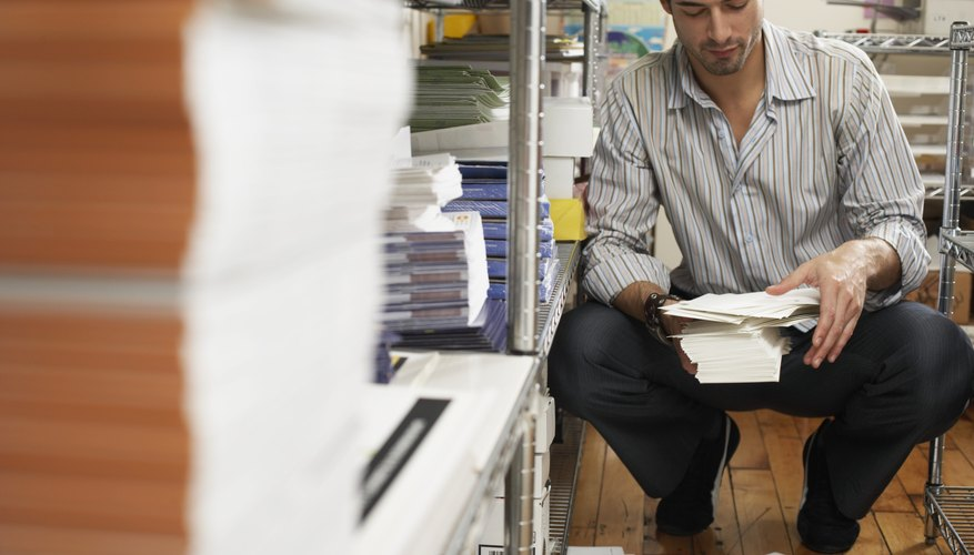 Male office worker gathering spilt envelopes by stationery shelving