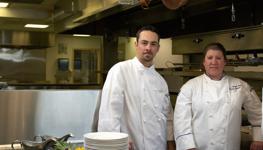 Portrait of male and female chef in commercial kitchen