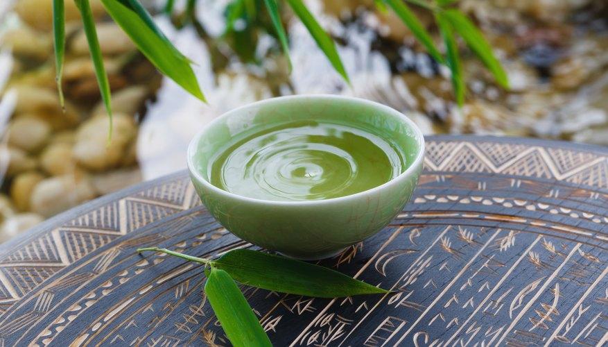 A cup of green tea on a tray near a stream.