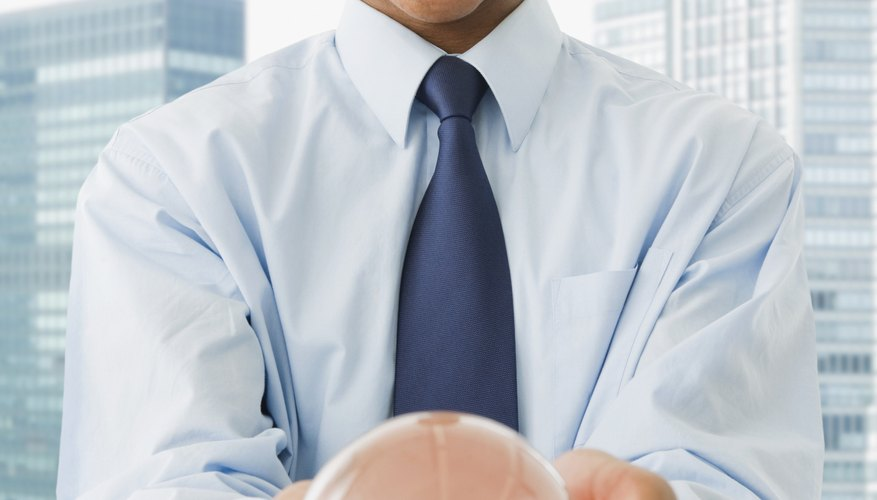 Mixed race businessman holding crystal ball