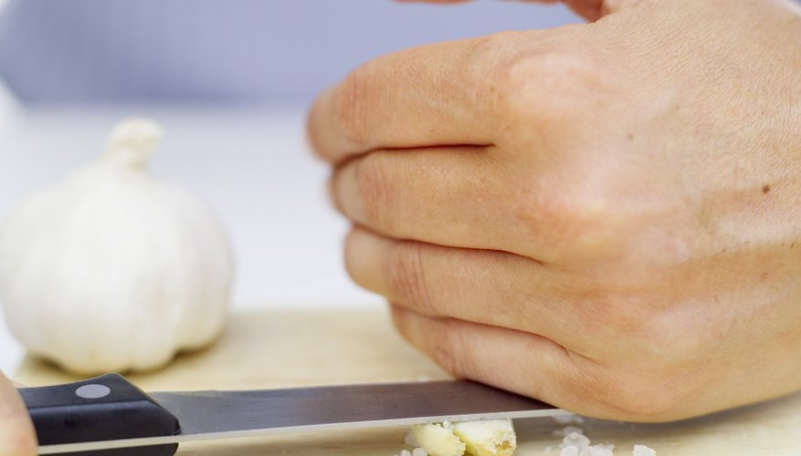 A woman crushes garlic with the side of a knife.