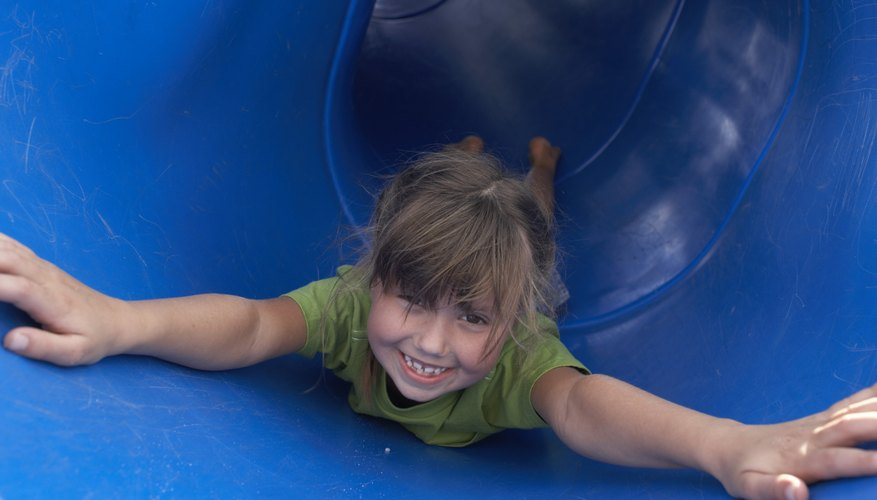 A girl happily slides down a plastic tube slide.
