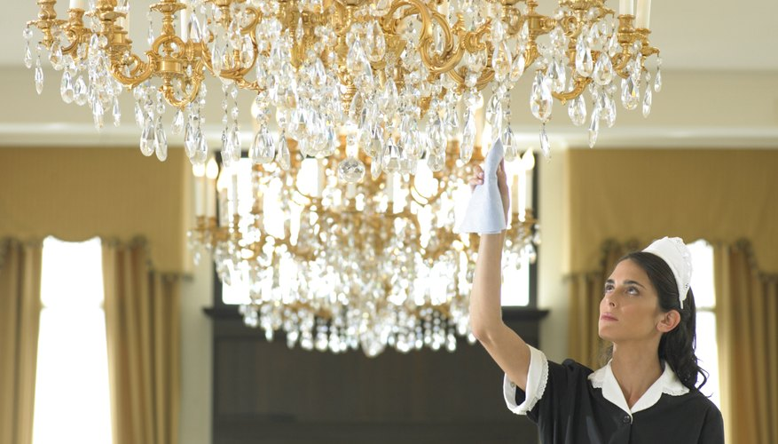 Maid cleaning foyer chandelier.