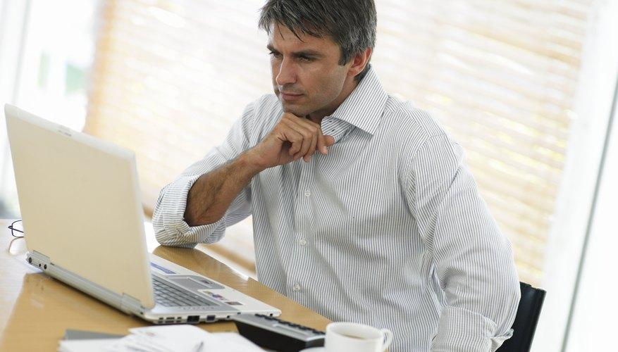 Man at desk, looking at laptop