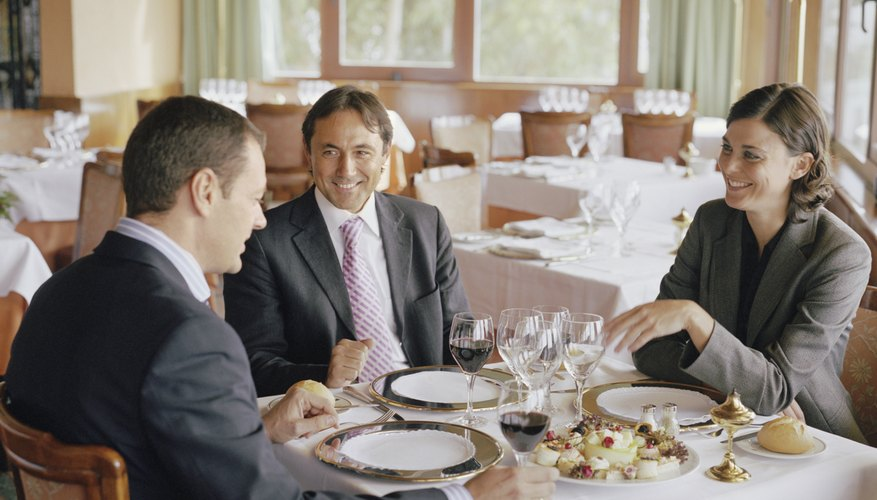Two businessmen and businesswoman at restaurant table, laughing