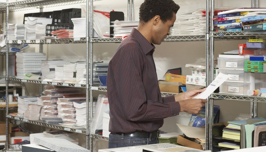 Male office worker by stationery storage shelves, reading document
