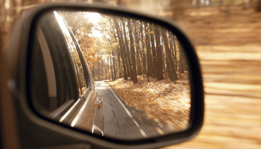 Autumn forest reflected in car side view mirror