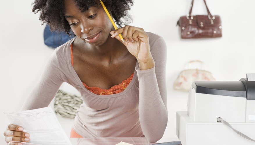 A young woman sits at her desk with a pencil and calculator and figures out her budget.