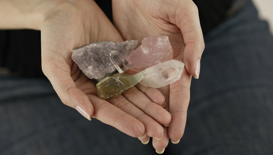 Woman holding various crystal stones in hands.
