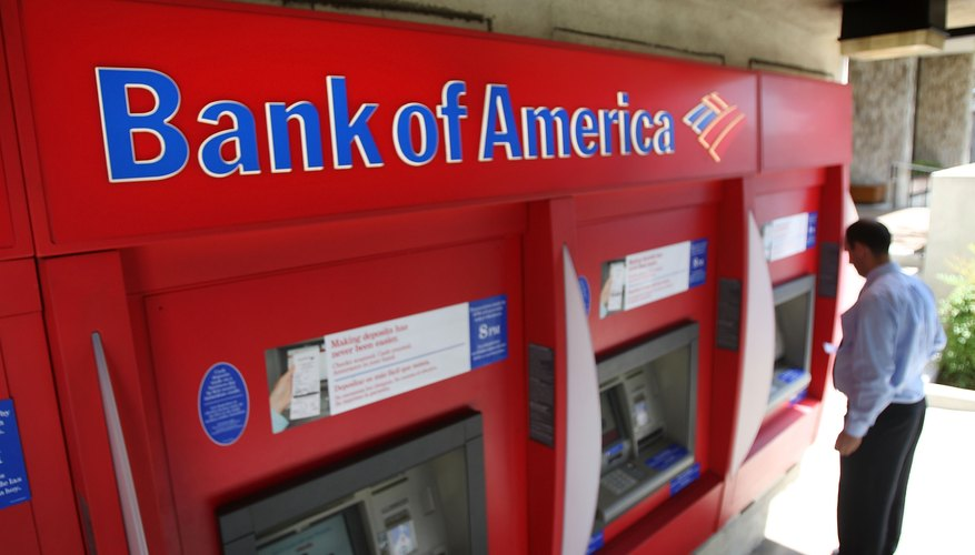 A man uses an ATM machine at a Bank of America branch.